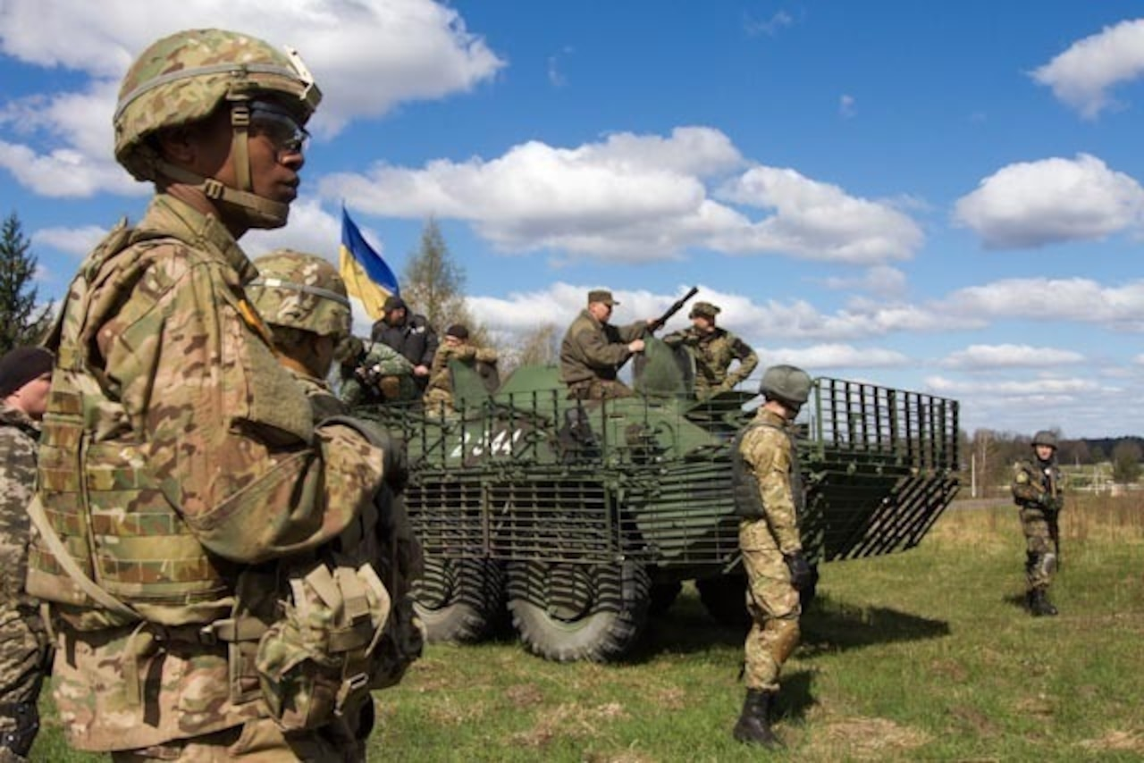 Soldiers from the U.S. Army's 173rd Airborne Brigade Combat Team and the Ukrainian national guard's 1st Battalion, 3029th take a break next to a BTR fighting vehicle, April 22, 2015, during exercise Fearless Guardian in Yavoriv, Ukraine. The 173rd ABCT trained several battalions of Ukrainian national guardsmen at the request of the Ukrainian government. U.S. Army photo by Sgt. Alexander Skripnichuk