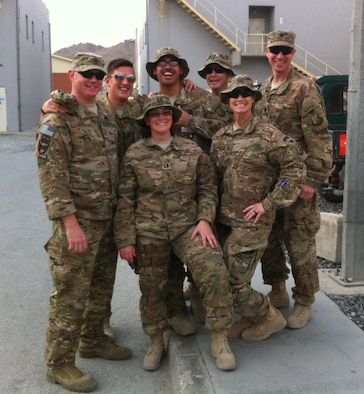 Capt. Eydie Sakura (middle front) and Maj. Phyllis Pelky (right front) stand with Train, Advise, Assist Command-Air (TAAC-Air) friends at Hamid Karzai International Airport, Kabul, Afghanistan. Pelky died in a helicopter crash at Headquarters Resolute Support Oct. 11, 2015. (U.S. Air Force courtesy photo/released).