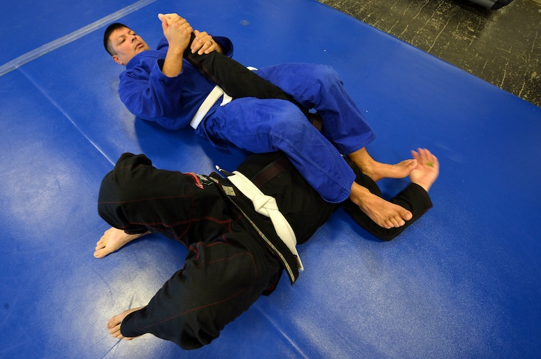 Two students of the Combatives House jiu-jitsu program practice their skills with the arm bar at Shaw Air Force Base, S.C., Nov. 14, 2015. The facility ran by volunteers offer free jiu-jitsu, boxing, cross-fit, extreme fitness classes, and Level I and Level II Army Combatives training. (U.S. Air Force photo by Senior Airman Diana M. Cossaboom)