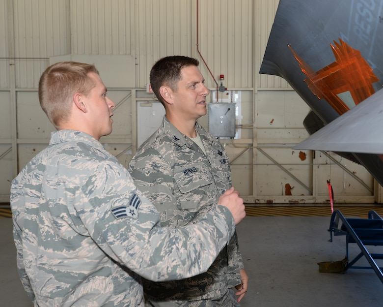 Senior Airman Hayden Johnson, low-observable aircraft maintenance technician, explains the process of applying LO coatings to Col. Joseph Kunkel, 325th Fighter Wing vice commander.  The coatings and molds used assist in the F-22s combat performance during missions, but require consistent and professional care in order to maintain its performance. (U.S. Air Force photo by Airman 1st Class Cody R. Miller/Released)