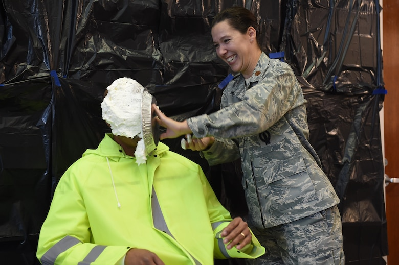 Gregory Walker, 460th Space Wing occupational safety manager, takes a pie in the face from Maj. April Reveteriano, 460th Space Wing Individual Mobilization Augmentee to the chief of safety, as a fundraiser for the Combined Federal Campaign Nov. 20, 2015, on Buckley Air Force Base, Colo. Buckley AFB held Wingman Day in order to recognize the men and women who continue the mission of the 460th Space Wing each and every day. (U.S. Air Force photo by Airman 1st Class Luke W. Nowakowski/Released)