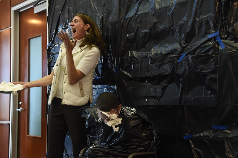 Chief Master Sgt. Brian Kruzelnick, 460th Space Wing command chief, takes a pie in the face from Christina Grooms, 460th Space Wing community support coordinator, as a fundraiser for the Combined Federal Campaign Nov. 20, 2015, on Buckley Air Force Base, Colo. Buckley AFB held Wingman Day in order to recognize the men and women who continue the mission of the 460th Space Wing each and every day. (U.S. Air Force photo by Airman 1st Class Luke W. Nowakowski/Released)