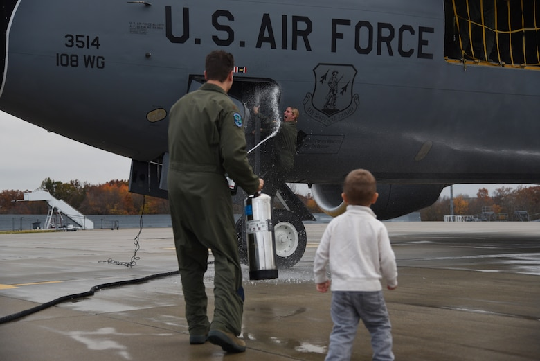 Capt. Sharon Gilliand, a KC-135 Stratotanker pilot with the 108th Wing, receives a celebratory spraying from her husband Maj. Kiel Gilliand, children Garrett and Lacey, fellow pilots and crew members following her final flight for the 108th Wing at Joint Base Mcguire-Dix-Lakehurst on Nov. 5, 2015. Gilliland, a pilot for 12 years with the New Jersey Air National Guard's 108th Wing is ceremonially hosed down by fellow pilots, crewmembers, friends and family as she leaves piloting to others and takes a non-flying job with the 514th AMOS, Air Force Reserve so she can devote more time to her family. During her time in the 108th Wing, Gilliland deployed three times and has 60 combat sorties to her credit. (U.S. Air National Guard photo by Master Sgt. Carl Clegg/Released)