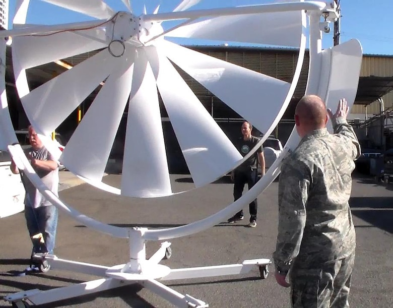 Natural Power Concepts personnel and Lt. Col. Scott Fitzner, of the AFRL Materials and Manufacturing Directorate, inspect the spoke wheel medium wind power system, one of a number of energy-harvesting technologies being installed as part of the five-year, $20 million cooperative agreement with AFRL that will establish a microgrid demonstration project at Joint Base Pearl Harbor-Hickam in Hawaii. (Courtesy photo/Hawaii Center for Advanced Transportation Technologies)