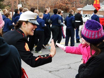 Sergeant Britteny L. Whitaker high-fives a young viewer of the Concord Christmas Parade in Concord, New Hampshire, Nov. 21. Marines and poolees of Recruiting Substation Concord led the parade for the day double-timing to cadence. Whitaker is the supply chief for Recruiting Station Portsmouth, NH.