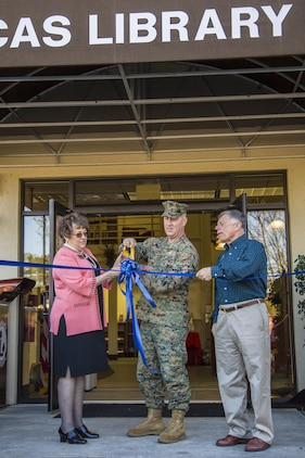 Rose Krauss, left, Col. Peter D. Buck, center, and Gary Cassevah, cut a ribbon during a ceremony for the reopening of the library aboard Marine Corps Air Station Beaufort Nov 23. The library finished a three-month renovation where the building, furniture and shelving were upgraded. The ceremony marked the official reopening of the library. Krauss is the supervisory librarian at MCAS Beaufort. Buck is the commanding officer of the air station. Cassevah is the director of Marine Corps Community Services.