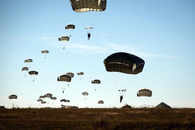 Army paratroopers descend to the ground at the Sicily drop zone on Fort Bragg, N.C., Nov. 21, 2015. The soldiers were participating in the Saturday Proficiency Jump Program, which aims to allow paratroopers to build additional proficiency and confidence for airborne operations. U.S. Army photo by Staff Sgt. Charles Crail