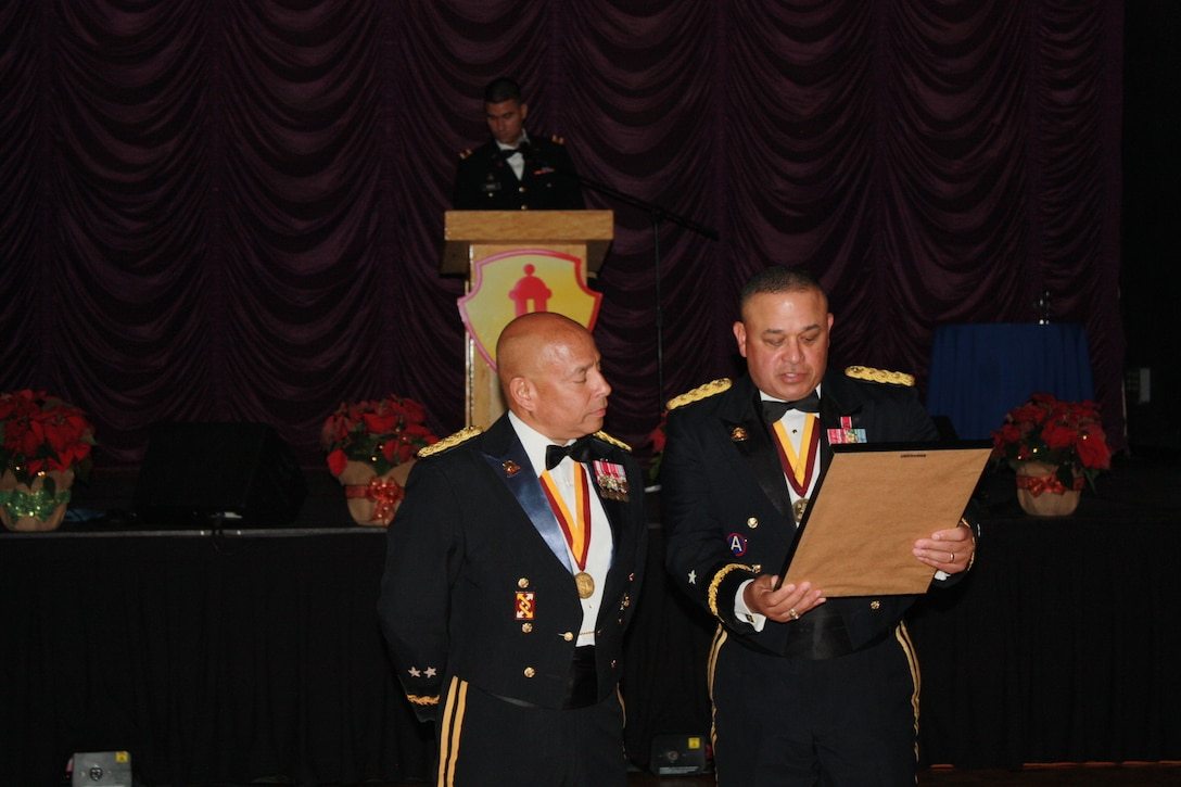 Brig. Gen. Jose R. Burgos, 1st MSC Commanding General, presents Maj. Gen. Luis R. Visot with a small memento of appreciation during the 2015 Military Ball at the Hilton Ponce Golf & Casino Resort in Ponce, Puerto Rico, Nov. 21, 2015.
