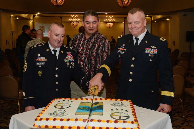 "Command Sgt. Maj. JamesPeter Matthews, Matthew ""Black Eagle Man"" Cordes and Brig. Gen. Scott Morcomb, Commanding General of the 11th Theater Aviation Command, cut cake during the National American Indian Heritage Month observance Nov. 20 at Fort Knox, Ky. U.S. Army Reserve soldiers from the 11th Theater Aviation Command (TAC), headquartered at Fort Knox, co-hosted this event in order to recognize the significant contributions that American Indians made to the establishment and growth of the U.S. The 11th Theater Aviation Command (TAC) is the only aviation command in the Army Reserve. The 11th TAC has two missions, functioning as both a warfighting headquarters and as a functional command. As warfighting command, the 11th TAC provides command & control, staff planning, and supervision for two aviation brigades and one air traffic service battalion. As a functional command the 11th TAC provides command and control for all Army Reserve Aviation. (Photo by Fort Knox Visual Information)"