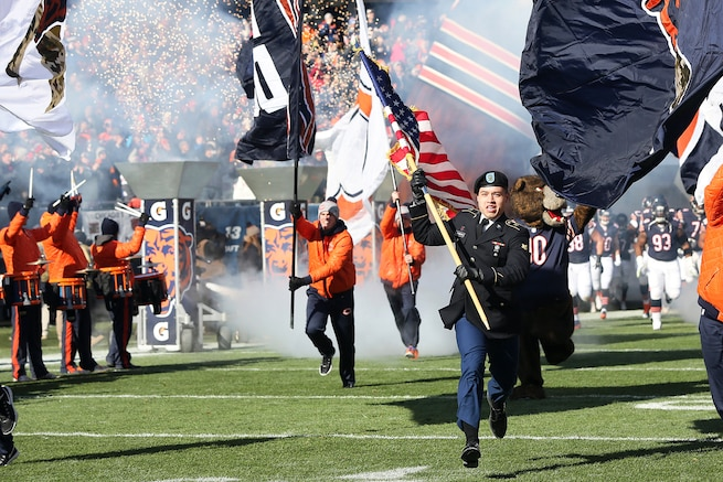 Army Spc. Leopoldo Guerrero leads the Chicago Bears onto Soldier Field at the start of the Bears game against the Denver Broncos in Chicago, Nov. 22, 2015. More than 100 service members participated in game-day activities honoring veterans at the stadium. Guerrero is assigned to the 814th Military Police Company.