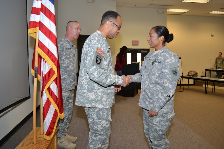 Command Sgt. Maj. Jeffrey Darlington, the 80th Training Command senior noncommissioned officer, looks on as Maj. Gen. A.C. Roper, commander 80th TC, congratulates Staff Sgt. Jadrian Whitfield, 100th Training Division, after Roper awarded her the Army Commendation Medal for winning the 80th TC Instructor Of the Year competition in the noncommissioned officer category during an award ceremony at Fort Knox, Ky., Nov. 7, 2015. Whitfield went on the win the IOY competition at the Army Reserve level, Nov. 23, 2015.