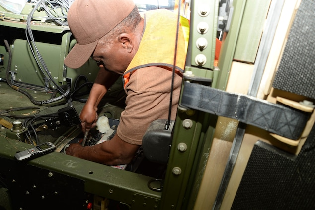 Melvin Williams, mechanic, Marine Corps Logistics Command, removes a battery from a vehicle recently while performing the level A preservation process aboard Marine Corps Logistics Base Albany. This is one step in an extensive process to help prevent deterioration of vehicles stored outside.