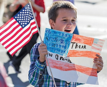Students from several schools, ranging from elementary to area colleges, waved flags and held banners as they marched in the annual Veterans Day Parade Nov. 11 in Manhattan, Kansas.
