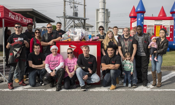 Members of the Endangered Species Motorcycle Club pose by the gift box during the third-annual Toy Drive and Motorcycle Rally at the Marine Thrift Store Nov. 22, 2015, at Marine Corps Air Station Iwakuni, Japan. Japanese motorcycle clubs, riders from the air station and station residents attended the event to donate toys for Japanese orphans and to participate in contests from best decorated bike to furthest traveled.