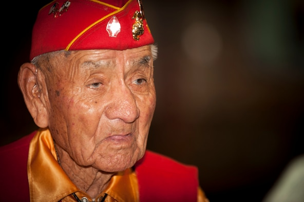 Former U.S. Marine Corps Navajo Code Talker George Willie looks on as his daughter tells his military story during the Native American Heritage Month Meeting at Nellis Air Force Base, Nev., Nov. 19, 2015. Willie enlisted in the Marine Corps shortly after the attack on Pearl Harbor in 1941 and went on to serve in a number of key battles, including the invasion of Okinawa in 1945. Navajo code talkers were recruited in order to ensure communications security against the Japanese, who had become adept at cracking U.S. codes. (U.S. Air Force photo by Senior Airman Joshua Kleinholz)