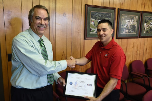 Dr. Don Sjoberg, superintendent of Poteau Public Schools, accepts the Employer Support of the Guard and Reserve Patriot Award Nov. 10, 2015, from 2nd Lt. Alcides Silva, 188th Force Support Squadron personnel officer and Poteau High School teacher, at Poteau, Okla. Sjoberg received the award for contributing to national security and protecting liberty and freedom by supporting employee participation in America's National Guard and Reserve force as a patriotic employer. (U.S. Air National Guard photo by Tech Sgt. Chauncey Reed/Released)