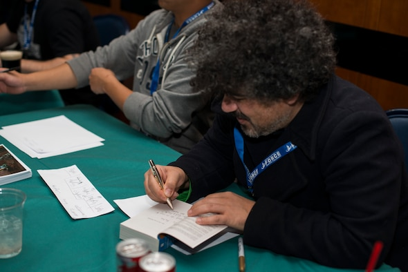 Miltos Yerolemou, film actor, autographs a Game of Thrones book during Operation Sci-Fi Con at Spangdahlem Air Base, Germany, Nov. 23, 2015. Yerolemou played Syrio Forel, sword master, in the TV adaptation of the book, Game of Thrones. (U.S. Air Force photo by Staff Sgt. Christopher Ruano/Released)