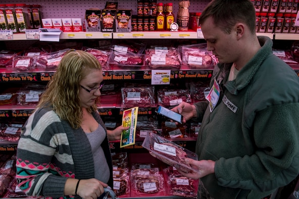 U.S. Army Sgt. Matthew O'Connor, 52nd Medical Group Spangdahlem NCO in charge of the Veterinary Clinic treatment facility, and his wife shop during the 2015 Commissary Sweep at Spangdahlem Air Base, Germany, Nov. 23, 2015. The contestants received 25 minutes to shop for groceries while also solving riddles during the event. (U.S. Air Force photo by Senior Airman Rusty Frank/Released)