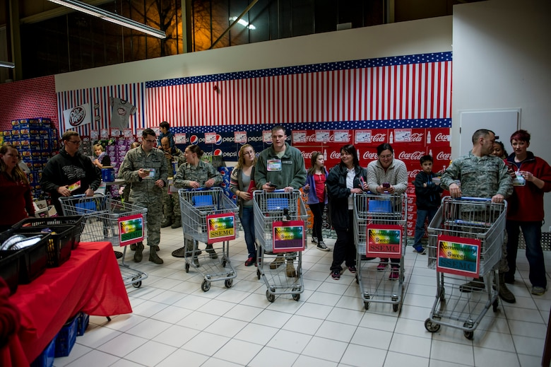 Contestants get ready to start shopping during the 2015 Commissary Sweep at Spangdahlem Air Base, Germany, Nov. 23, 2015. The participants were chosen during the deployed family member Thanksgiving dinner from five different categories which are unaccompanied Airman, accompanied Airman, accompanied Airman with one-two kids, accompanied Airman with three or more and Spangdahlem Spouses Enlisted Members Club. (U.S. Air Force photo by Senior Airman Rusty Frank/Released)