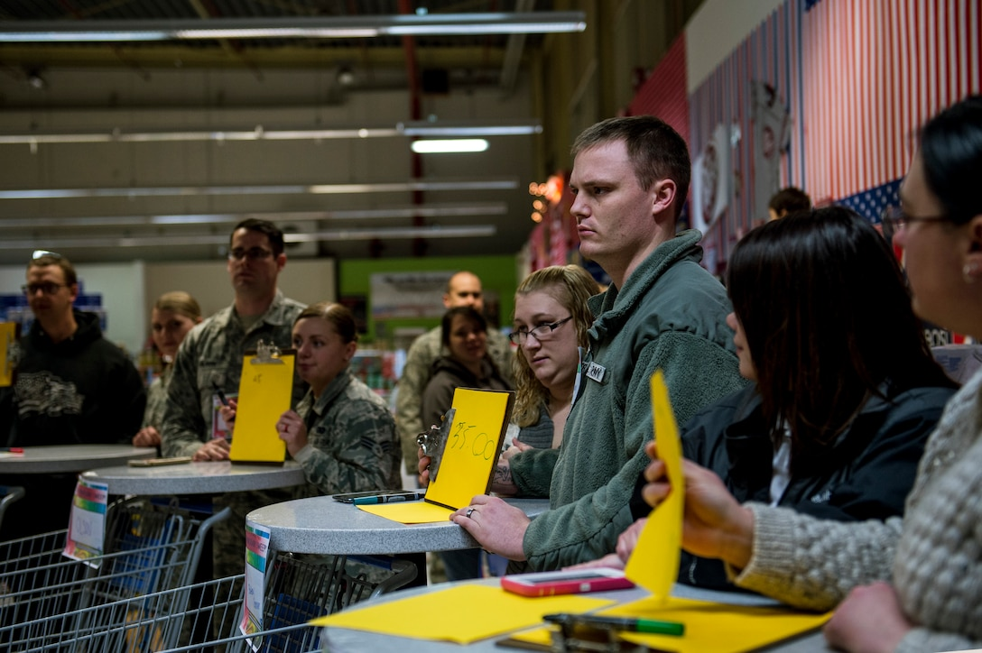 Event participants hold a piece paper with a price on it during the 2015 Commissary Sweep at Spangdahlem Air Base, Germany, Nov. 23, 2015. The event allowed the contestants to shop for groceries, solve riddles and have fun. (U.S. Air Force photo by Senior Airman Rusty Frank/Released)