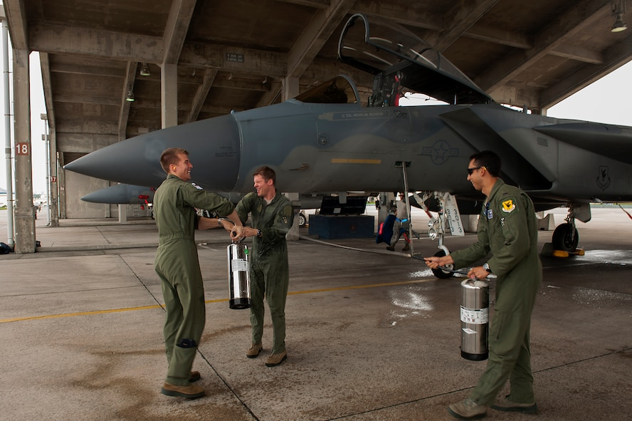 U.S. Air Force Lt. Col. Alexander Haddad, 44th Fighter Squadron pilot, gets sprayed with water by 1st Lt. Maxwell Anthony (left) and 1st Lt. Michael Tope (right), 44th FS pilots, after Haddad reached 2,000 flying hours, Nov. 19, 2015, at Kadena Air Base, Japan. It is a tradition for pilots to get sprayed down with water after reaching a significant milestone.. (U.S. Air Force photo by Airman 1st Class Corey M. Pettis)