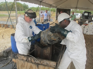 Workers flush munitions with hot water and MuniRem during inertion operations Nov. 4. Liquids carry black powder down a stepped trough system, which was built with 2-by-4s onsite. The stepped system is a means for collecting progressively finer black powder particulates, which are then scooped and further contained.