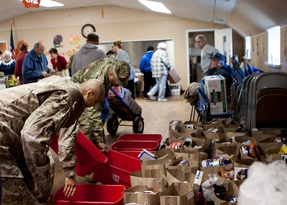 Military members stationed at Defense Distribution Center, Susquehanna, work to load meals to be delivered to shut-ins at the West Shore Senior Center on Nov. 20.