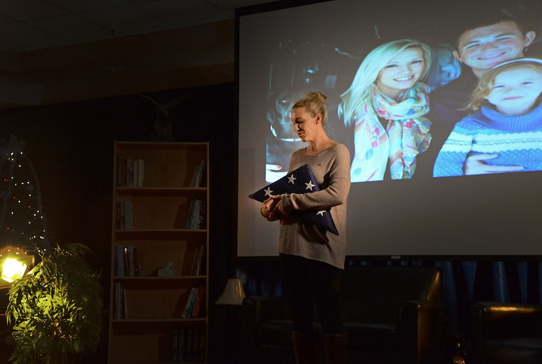 Samantha Lewis, widow of the late Staff Sgt. Jordan Lewis, tightly hugs a folded flag while sharing her story of loss during the second Storytellers Nov. 19, 2015, at Cannon Air Force Base, N.M. Lewis recounted Jordan's passing, who tragically lost his life during a training accident at Melrose Air Force Range May 11, 2015. (U.S. Air Force photo/Staff Sgt. Alexx Pons)