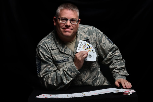 U.S. Air Force Master Sgt. Scott Fridinger, additional duty first sergeant assigned to the Air Combat Command Communications Support Squadron, displays a royal flush at Langley Air Force Base, Va., Oct. 21, 2015. Fridinger uses magic to build rapport with his airmen and enhance morale. U.S. Air Force photo by Senior Airman Aubrey White