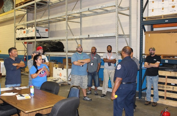 DLA Distribution Corpus Christi, Texas, employees receive a presentation on fire extinguisher training from Naval Air Station fire inspector Maurice Phillips.