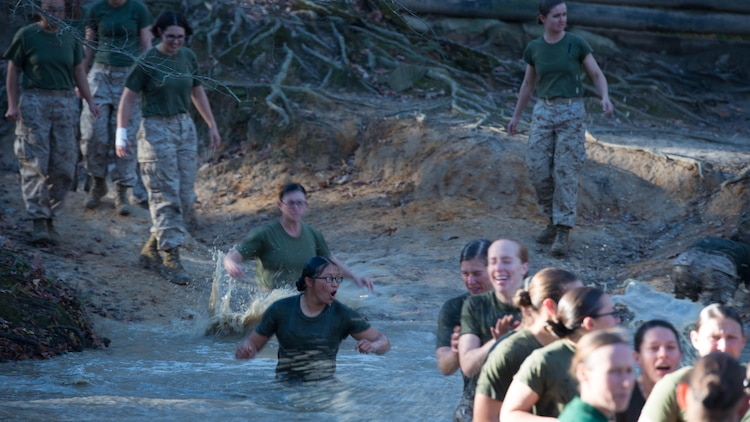 Candidates in Officer Candidate School jump into a muddy pit right before receiving their Eagle, Globe and Anchor at Marine Corps Base Quantico, Virginia, Nov. 20, 2015. The candidates of Class 0CC-220 graduated and were commissioned as second lieutenants during the 75th anniversary of OCS on Brown Field. (U.S. Marine Corps photo by Sgt. Eric Keenan)