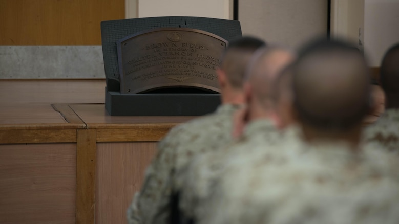 A plaque dedicated to 2nd Lt. Walter V. Brown sits in front of candidates of Officer Candidate School learning about Marine officer history at Marine Corps Base Quantico, Virginia, Nov. 20, 2015. Brown, a former squadron commander, was killed in a crash during an exercise at Quantico,  on June 9, 1921. (U.S. Marine Corps photo by Sgt. Eric Keenan)