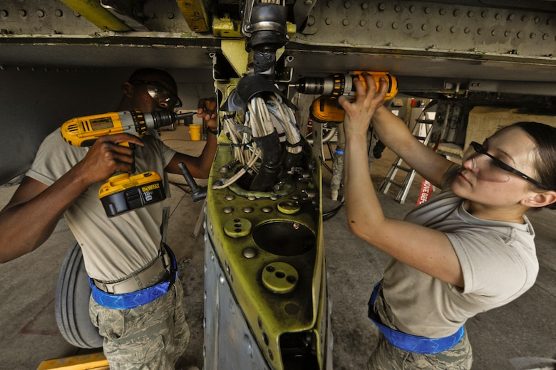 U.S. Air Force Airman Derrick Coakley (left) and Senior Airman Sophia Ramallo perform maintenance on an A-10C Thunderbolt II aircraft at Kandahar Air Field, Afghanistan, on Dec. 27, 2009.  Coakley and Ramallo are assigned to the 451st Expeditionary Maintenance Squadron.  DoD photo by Tech. Sgt. Efren Lopez, U.S. Air Force.  (Released)