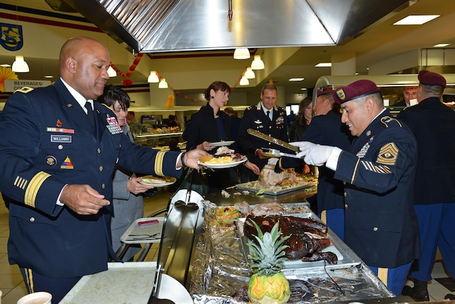 U.S. Army Sgt. 1st Class Norberto Badillo, right, serves a Thanksgiving lunch to U.S. Army Maj. Gen. Darryl A. Williams, commander of U.S. Army Africa, during a celebration in Vicenza, Italy, Nov. 24, 2015. Badillo is a paratrooper assigned to the 173rd Brigade Support Battalion, 173rd Airborne Brigade. U.S. Army photo by Davide Dalla Massara