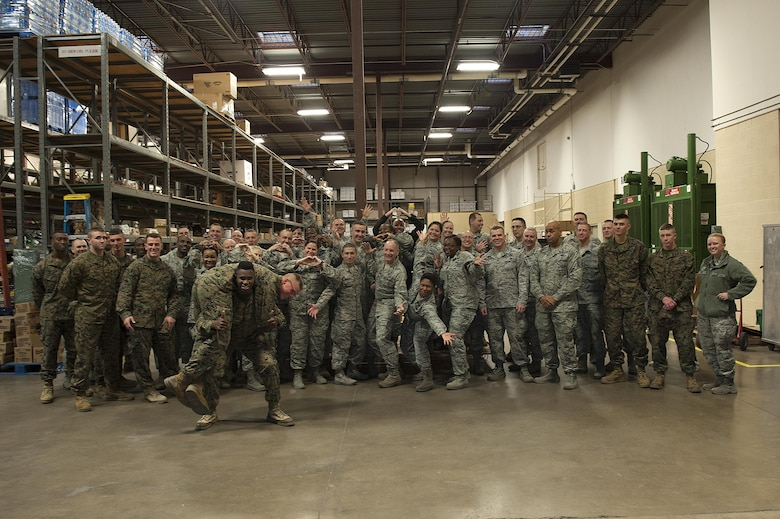 Volunteers for Operation Warmheart pose for a group photo at the Commissary on Goodfellow Air Force Base, Texas, Nov. 24, 2015. Leadership from almost all squadrons on base came to volunteer their help in building baskets to ease the cost of Thanksgiving dinner for permanent party and civilians workers on base. (U.S. Air Force photo by Airman 1st Class Caelynn Ferguson/Released)