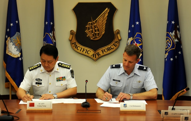 JOINT BASE PEARL HARBOR-HICKAM, Hawaii (Nov. 25, 2015) - U.S. Air Force Col. Brian Delamater, Chief of Pacific Air Forces Advanced and Warfighter Integration Division, and Senior Captain Liang Yang, Deputy Director Operations Department, Navy Headquarters, Peoples Liberation Army, sign the meeting minutes for the bi-annual Military Maritime Consultative Agreement (MMCA) talks, held Nov. 21-24, at Headquarters, Pacific Air Forces. The bilateral MMCA talks are a long-standing mechanism designed to provide open and transparent communication to address concerns and develop common understandings between U.S. and PRC air and naval forces in order to avoid unsafe incidents and minimize risk. (Photo by U.S. Pacific Air Forces Public Affairs)