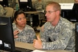 Master Sgt. Maria Ramos, an instructor for phase 1 of the 94th Training Division's Finance Senior Leaders Course at Fort Dix, New Jersey, helps Sgt. 1st Class Marion Fox prepare to teach a block of instruction to his fellow classmates as part of his training.  Ramos is a guest instructor from 7th Battalion, 95th Regiment out of Grand Prairie, Texas.