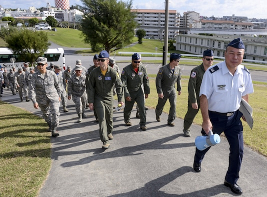 Japan Air Self-Defense Force Lt. Col. Yutaka Hori, 83rd Wing Headquarters director of administration, leads Kadena Airmen up a hill to observe a historical site Nov. 20, 2015, at Naha Air Base, Japan. The U.S. Airmen were provided an extensive tour of the base as part of a wing exchange program, held to improve the understanding of each Air Force's mission and capabilities. (U.S. Air Force photo by Senior Airman John Linzmeier/Released)