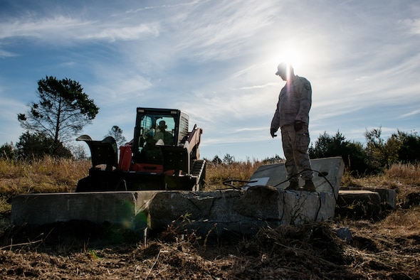 Airmen from the civil engineering squadrons of the 137th Air Refueling Wing, Oklahoma City, and the 138th Fighter Wing, Tulsa, Okla., evaluate the extent of on-site debris during a debris clearance training at Camp Gruber, Oct. 19-23, 2015. The primary goal for the training was to familiarize Airmen with the equipment they will use during a real-world emergency.