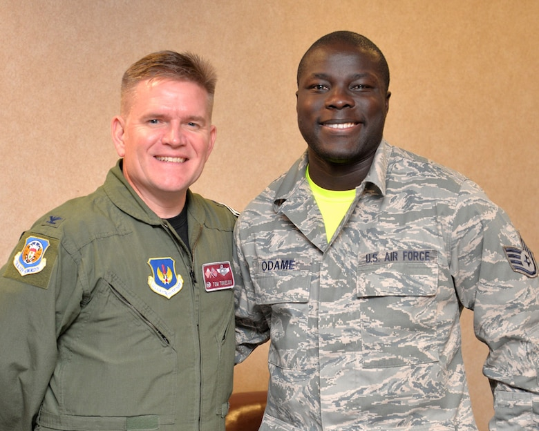 U.S. Air Force Staff Sgt. Richard Odame, right, 727th Air Mobility Squadron air freight supervisor, stands with U.S. Air Force Col. Thomas D. Torkleson, 100th Air Refueling Wing commander, after being presented a Commander's Coin, Nov. 13, 2015, on RAF Mildenhall. Odame helped a cyclist who had been hit by a motorist, Nov. 2, 2015, along the A1101 near Mildenhall, England. Odame ensured the cyclist was kept conscious and warm while directing traffic until the local emergency services arrived. (U.S. Air Force photo by Karen Abeyasekere/Released)