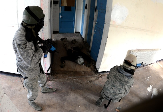 "U.S. Air Force Staff Sgt. Shannon Smith, left, 100th Maintenance Group maintenance analyst, and U.S. Air Force Airman 1st Class Nicholas Vidmar, 100th Aircraft Maintenance Squadron crew chief, practice the ""fight"" response to an active shooter during expeditionary active shooter training Nov. 23, 2015, on RAF Feltwell, England. The new training, implemented Oct. 1, is designed to prepare deploying Airmen for an environment where firearms are potentially more prevalent, meaning they might be armed and have to protect themselves and others from the threat of an active shooter. (U.S. Air Force photo by Senior Airman Kate Thornton/Released)"