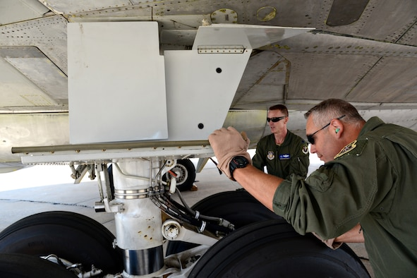 Lt. Col. Brian Rhodarmer and Senior Master Sgt. Tim Brown inspect flight controls on an E-3 AWACS, looking for any kind of leaks or for any components that may not be hooked up properly. (Air Force photo by Kelly White/Released)