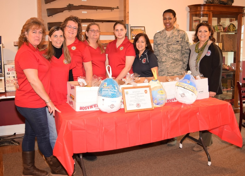 American Legion Post 10 Auxiliary members and Horsham Air Guard Station's Airman and Family Readiness office representatives surround a table of abundant Thanksgiving meal donations to the 111th Attack Wing in Fort Washington, Pennsylvania on Nov. 21, 2015. Janis Navo, Auxiliary president (left) will be kicking off  the post's Christmas drive to fulfill wish lists for the USO. (U.S. Air National Guard photo by Master Sgt. Christopher Botzum/Released)