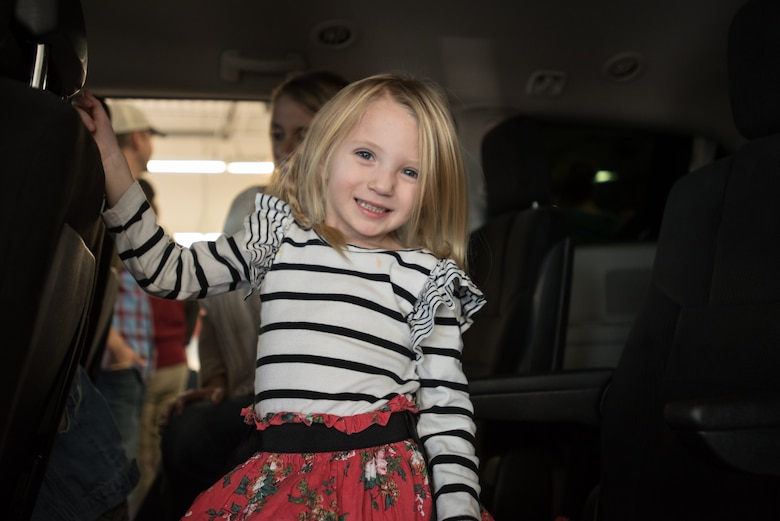 """Ava Goodlin, the 3-year-old daughter of Staff Sgt. Neil Goodlin, checks out her family's new minivan during an unveiling ceremony at Oxmoor Collision Center in Louisville, Ky., Nov. 20, 2015. The van was donated to Neil Goodlin, a fire team member in the Kentucky Air National Guard's 123rd Security Forces Squadron, as part of the National Auto Body Council's """"Recycled Rides"""" program, which restores wrecked vehicles to like-new condition before giving them to needy individuals. (U.S. Air National Guard photo by Maj. Dale Greer)"""
