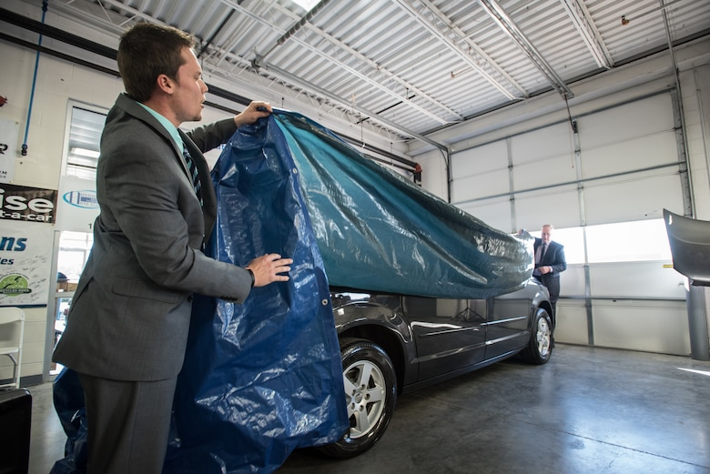 Jeff Lemr (left), manager of Oxmoor Collision Center, and Del Farmer, chief operating officer of Oxmoor Auto Group, unveil a restored Dodge Caravan at Oxmoor Collision in Louisville, Ky., Nov. 20, 2015. The van was being donated to Staff Sgt. Neil Goodlin, a fire team member in the Kentucky Air National Guard's 123rd Security Forces Squadron, as part of a program that restores wrecked vehicles to like-new condition before giving them to needy individuals. (U.S. Air National Guard photo by Maj. Dale Greer)