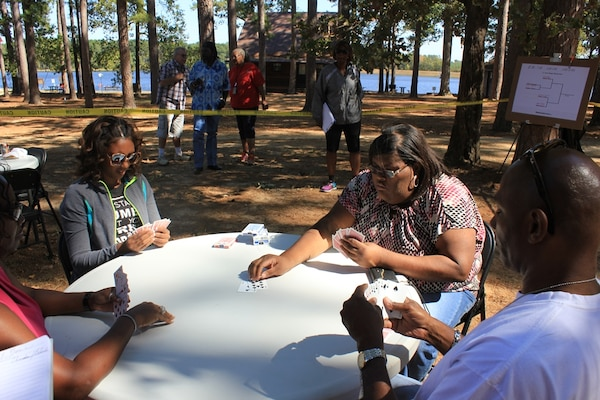 Turkieshiejia Nelson, Chanda Henderson, and Marshall Williams, DLA Distribution Red River, Texas, employees play spades at the annual Employee Appreciation Day on Oct.16.