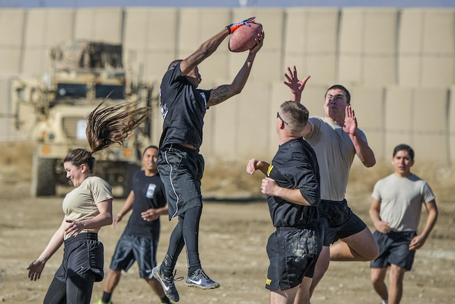 "U.S. soldiers play U.S. airmen in a friendly ""Turkey Bowl"" football game on Bagram Airfield, Afghanistan, Nov. 26, 2015. The soldiers are assigned to Florida Army National Guard's 1st Battalion, 265th Air Defense Artillery Regiment, and the airmen are assigned to Florida Air National Guard's 290th Joint Communications Support Squadron. The Army team won the game 42-35. U.S. Air Force photo by Tech. Sgt. Robert Cloys"