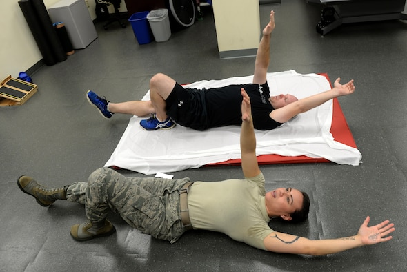 Staff Sgt. Amber Coley, a 4th Medical Operations Squadron physical therapy technician, demonstrates an exercise for Tech. Sgt. Jared Rhynehart, a 4th Aircraft Maintenance Squadron lead support team member, during a rehabilitation session, Nov. 18, 2015, at Seymour Johnson Air Force Base, North Carolina. The physical therapists assign several different exercises per session with difficulty dependent on the patient's injury or pain area. (U.S. Air Force photo/Airman 1st Class Ashley Williamson)