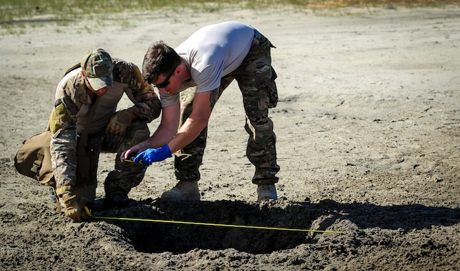 Staff Sgt. Michael Alger and Airman 1st Class John Nipp, both explosive ordnance disposal Airmen with the 1st Special Operations Civil Engineer Squadron, measure a blast hole during post-blast analysis training at Hurlburt Field, Fla., Nov. 19, 2015. A post-blast analysis takes place when an improvised explosive device detonates and EOD Airmen arrive on scene to determine what happened. (U.S. Air Force photo/Senior Airman Meagan Schutter)