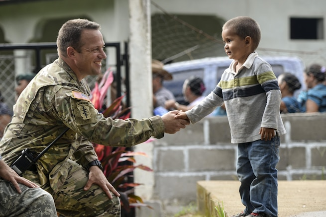U.S. Army Capt. John Dills shakes hands with a boy during a medical readiness training exercise in San Jose De Rio Pinto, Honduras, Nov. 12, 2015. Dills is the tactical officer in charge. The exercise provides military members with essential training in austere locations and helps build local community relations in the host country. U.S. Air Force Photo by Senior Airman Westin Warburton